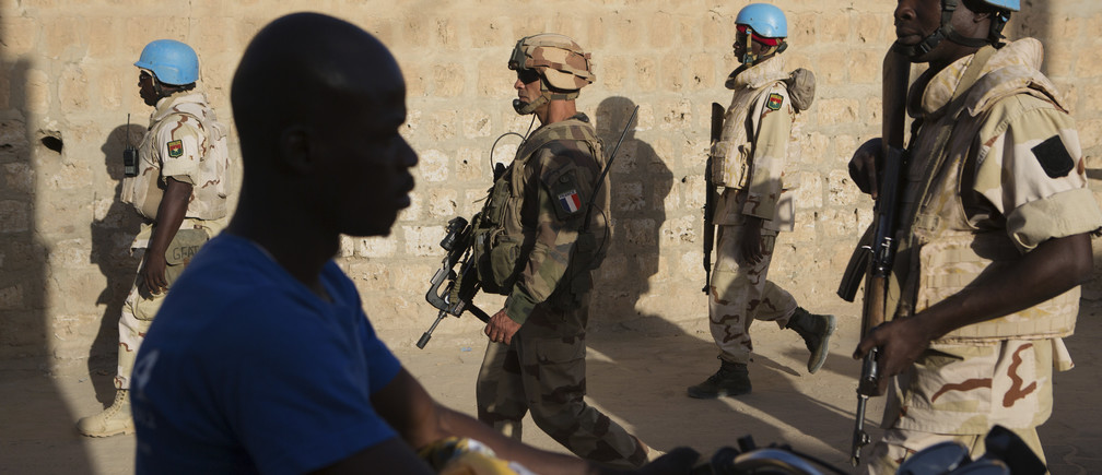 French soldiers and United Nations peacekeepers from Burkina Faso patrol in Timbuktu, Mali, November 5, 2014. If the French army and its allies are to keep al Qaeda at bay in the desert of northern Mali they must stop them seizing the biggest prizes in the sea of white sand - the wells. So this month a column of soldiers from France, Burkina Faso and Mali, in armoured vehicles and pick-up trucks, churned toward a village north of Timbuktu where herders water camels and goats. They were looking for signs of infiltration by militants who 5need water as much as the locals do and aim to convert villages to their ideology. Picture taken November 6, 2014. REUTERS/Joe Penney (MALI - Tags: MILITARY CIVIL UNREST) - GM1EABL1S0M01