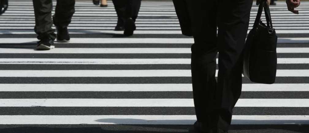 Pedestrians cross a road at Tokyo's business district September 30, 2014. Japanese big manufacturers' confidence improved slightly in the three months to September, a closely watched central bank survey showed, but service-sector sentiment worsened, adding to evidence that a sales tax hike continues to weigh on the economy. Picture taken September 30, 2014. To match JAPAN-ECONOMY/TANKAN