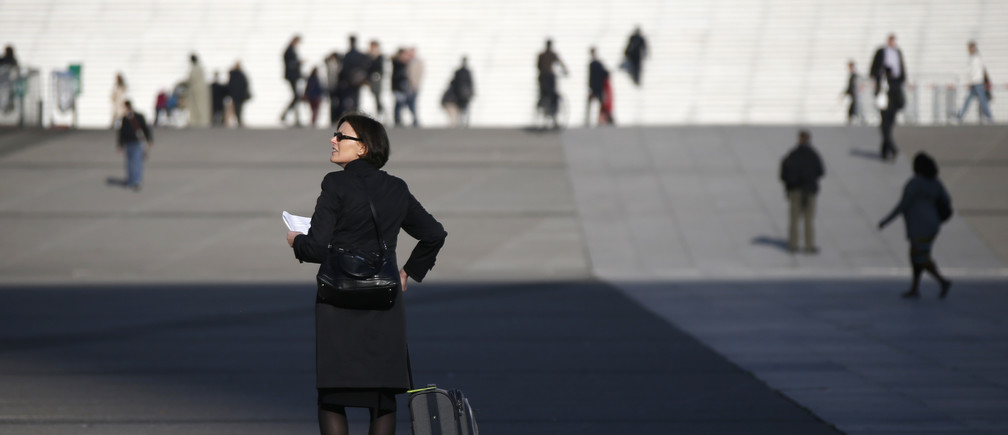 A businesswoman walks on the esplanade of La Defense, in the financial and business district in La Defense, west of Paris April 10, 2014.