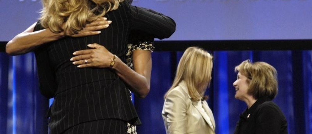Michelle Obama (second L) hugs Ann Romney as Elizabeth Edwards (far R) and Jeri Thompson mingle following a panel discussion amongst presidential candidate spouses at The Women's Conference 2007 in Long Beach, California, October 23, 2007. REUTERS/Chris Pizzello (UNITED STATES) - GM1DWLAUDSAA