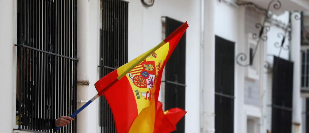 Una mujer agita una bandera española desde la ventana de su casa en apoyo a los trabajadores de la salud, durante el encierro en medio del brote de la enfermedad coronavirus (COVID-19), en Ronda, al sur de España, el 17 de abril de 2020.