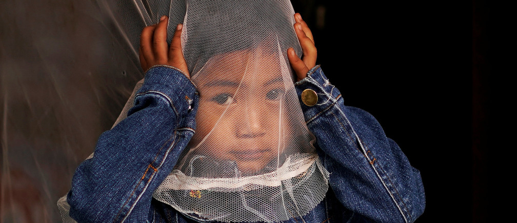 An ethnic Lisu little girl plays with a mosquito net in Lazimi village of Nujiang Lisu Autonomous Prefecture in Yunnan province, China March 24, 2018. Picture taken March 24, 2018. REUTERS/Aly Song - RC12F0051A70