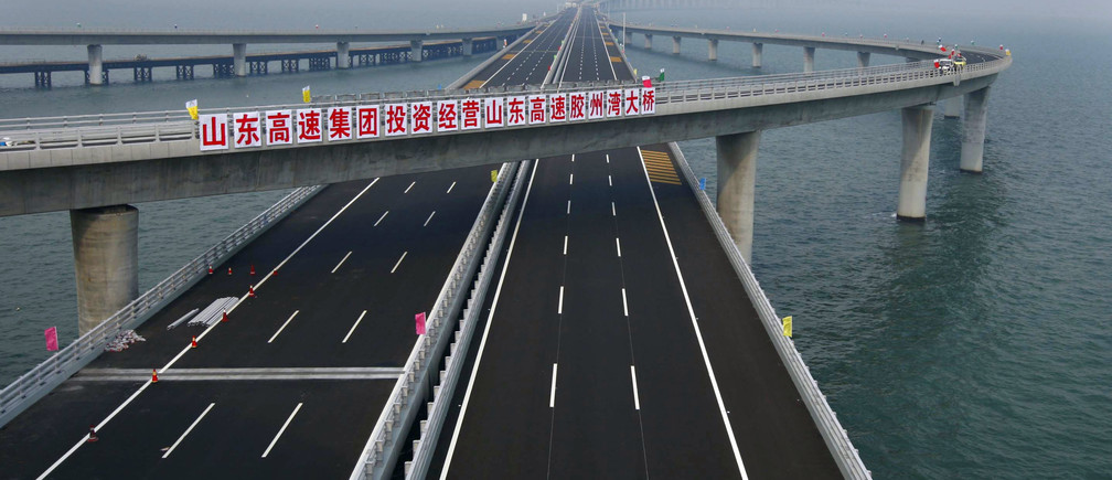 "A sign that reads: ""Shandong Highway Corp. invests to operate Shandong Highway Jiaozhou Bay Bridge"" is seen at Qingdao Jiaozhou Bay Bridge in Qingdao, Shandong province June 27, 2011. The world's longest sea bridge spanning Jiaozhou Bay of Qingdao City, Shandong Province, opened on Thursday, June 30, 2011. The bridge is 36 km (22 miles) long, Xinhua News Agency reported. Picture taken June 27, 2011.          REUTERS/China Daily   (CHINA - Tags: SOCIETY) CHINA OUT. NO COMMERCIAL OR EDITORIAL SALES IN CHINA - GM1E76U1I1G01"