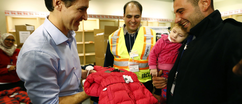 Syrian refugees are presented with a child's winter jacket by Canada's Prime Minister Justin Trudeau on their arrival in Toronto in 2015.
