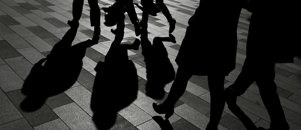 Workers cast shadows as they stroll among the office towers Sydney's Barangaroo business district in Australia's largest city, May 8, 2017.  REUTERS/Jason Reed - RC174F389170