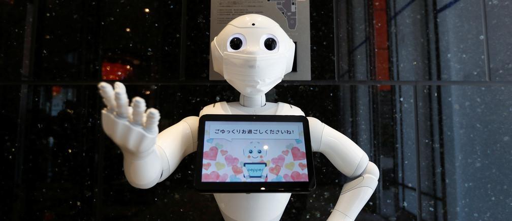 Un robot humanoide Pepper, fabricado por SoftBank Group Corp. demuestra cómo registrarse en un hotel de APA Group que ha sido designado para alojar a personas asintomáticas y con síntomas leves de la enfermedad coronavirus (COVID-19) para liberar camas de hospital y aliviar el trabajo de las enfermeras y los miembros del personal, en Tokio, Japón, el 1 de mayo de 2020.