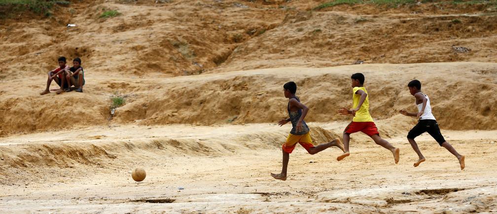 Rohingya refugee boys play football at the Kutupalang Makeshift Refugee Camp in Cox's Bazar, Bangladesh, July 8, 2017. REUTERS/Mohammad Ponir Hossain - RTX3ANOJ