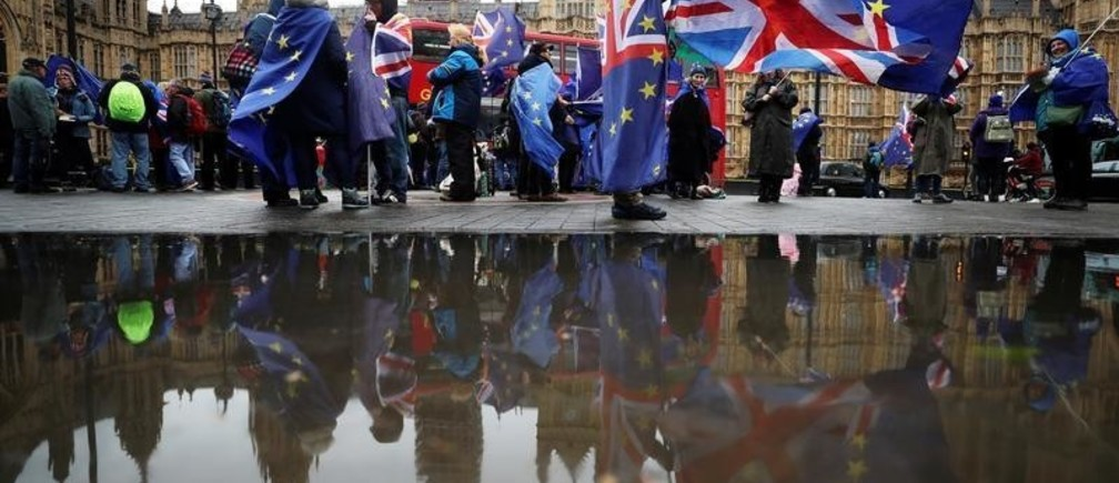 Anti-Brexit protesters are reflected in a puddle as they demonstrate opposite the Houses of Parliament in London, Britain, April 30, 2018.