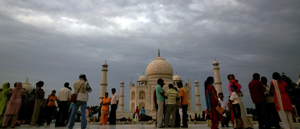 Tourists stand in front of the historic Taj Mahal in the northern Indian city of Agra July 11, 2007