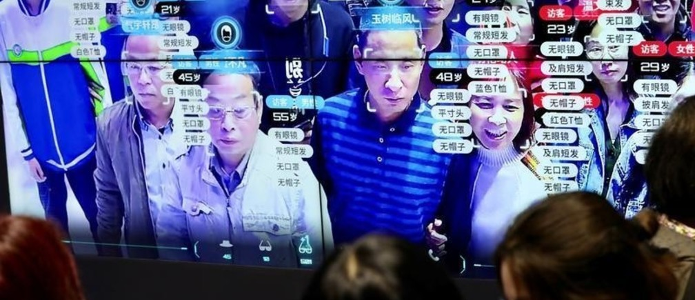 Visitors are seen at a screen displaying facial recognition technology at the Digital China Exhibition in Fuzhou, Fujian province, China May 8, 2019. China Daily via REUTERS  ATTENTION EDITORS - THIS IMAGE WAS PROVIDED BY A THIRD PARTY. CHINA OUT. NO COMMERCIAL OR EDITORIAL SALES IN CHINA. TPX IMAGES OF THE DAY - RC184FE55330