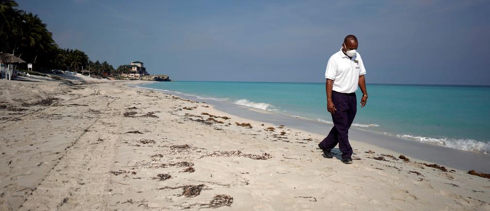 Un agente de seguridad con una máscara protectora camina por la playa en medio de la preocupación por la propagación de la enfermedad coronavirus (COVID-19), en Varadero, Cuba, el 10 de abril de 2020.