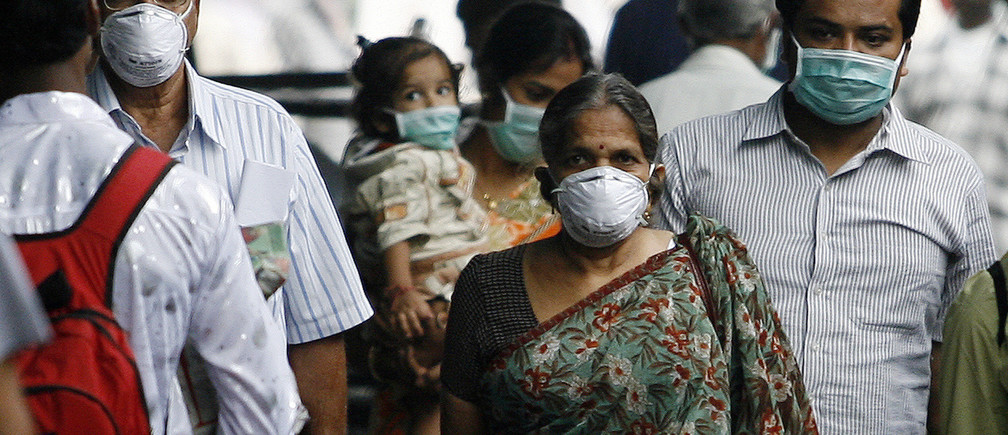 Travellers with masks walk on a railway platform in Pune August 18, 2009. Pune has reported the highest number of deaths caused by H1N1 influenza virus in India, according to a government statement released on Monday.    REUTERS/Arko Datta (INDIA SOCIETY HEALTH) - GM1E58I17RJ01