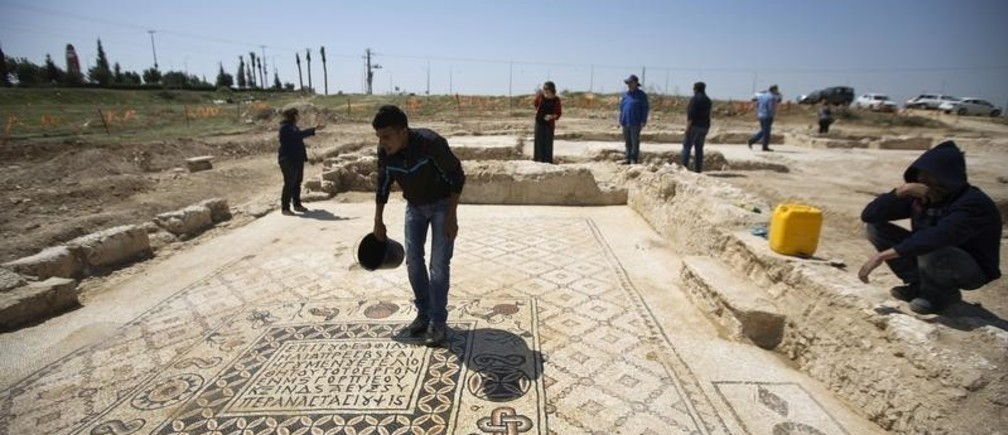 A worker for the Israel Antiquities Authority (IAA) stands on the mosaic floor of a monastery unearthed during excavations in Hura, east of Beersheba April 1, 2014. The IAA said on Tuesday that the Byzantine-era monastery and the mosaic floor were discovered during a salvage dig ahead of construction of an interchange. REUTERS/Amir Cohen (ISRAEL - Tags: RELIGION SOCIETY) - GM1EA411NO201