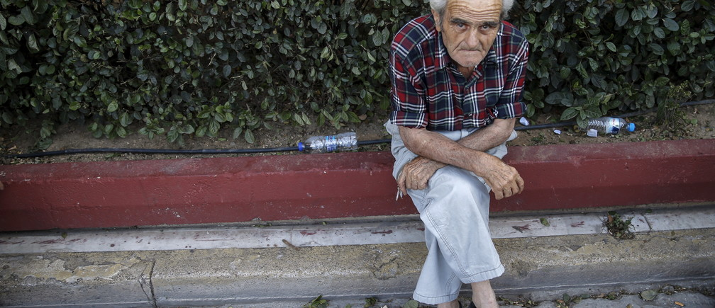 A pensioner rests during an anti-austerity demonstration in Athens, Greece June 23, 2015. Greek lawmakers reacted angrily on Tuesday to concessions Athens offered in debt talks and parliament's deputy speaker warned the proposals might be rejected, puncturing optimism that a deal to pull Greece back from the abyss might be sealed quickly. REUTERS/Marko Djurica - GF10000136949