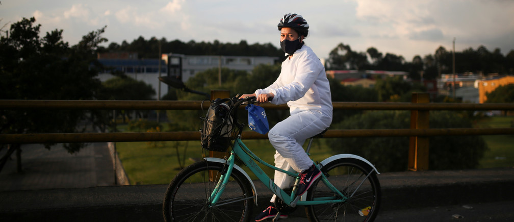 Una mujer que lleva un traje de bioseguridad y una máscara facial monta su bicicleta durante la hora punta, después de que el gobierno permitiera a ciertos sectores volver al trabajo, en medio del brote de la enfermedad coronavirus (COVID-19) en Bogotá, Colombia, el 11 de mayo de 2020.