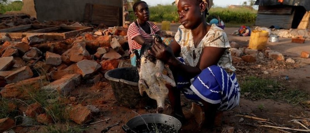 """Maria Jofresse, 25, watches her mother Ester Thoma preparing food beside their damaged house in the aftermath of Cyclone Idai, in the village of Cheia, which means """"Flood"""" in Portuguese, near Beira, Mozambique April 4, 2019. Maria Jofresse lost her two children to the storm. In the midst of the floods, she dug their small graves but can't find them anymore. """"People suffered indeed but no one suffered as I did because I lost the most precious things I had - my kids,"""" she said. REUTERS/Zohra Bensemra  SEARCH """"BENSEMRA FLOOD"""" FOR THIS STORY. SEARCH """"WIDER IMAGE"""" FOR ALL STORIES. - RC1D611B3F40"""