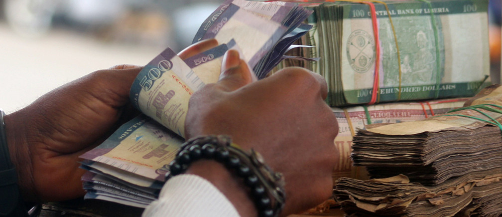 A money changer counts banknotes in Monrovia, Liberia September 21, 2018.