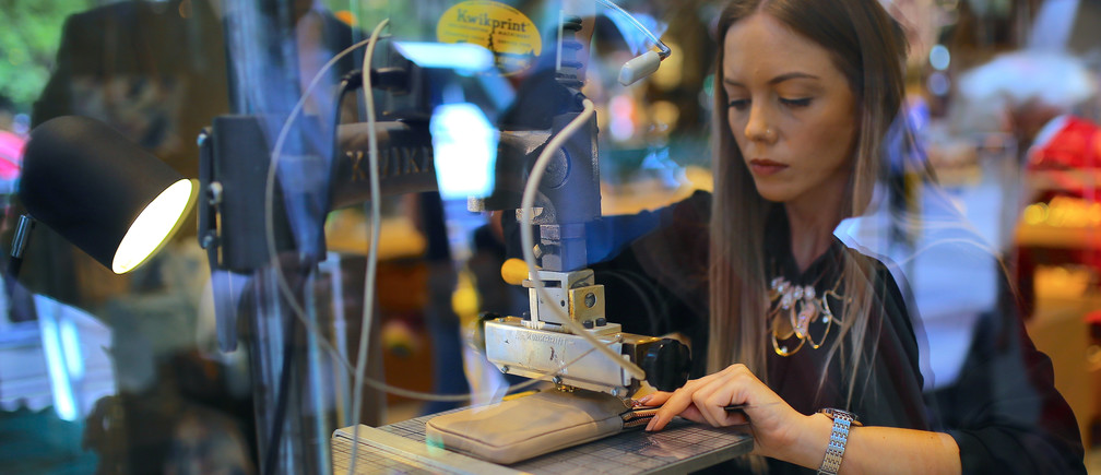 A woman uses a machine to emboss a wallet in the window of a retail store selling leather goods in central Sydney, Australia, November 15, 2017.