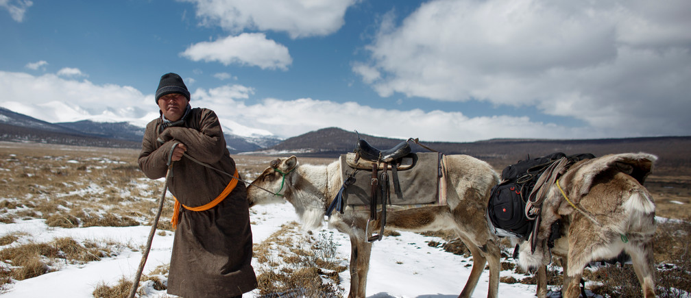 """Dukha reindeer herder Erdenebat Chuluu rests on a stick as he travels with his animals to visit neighbours near the village of Tsagaannuur, Khovsgol aimag, Mongolia, April 19, 2018. Chuluu has lived all his life in the centuries-old tradition of his Dukha ancestors, renowned for their reindeer-herding and hunter-gathering skills in the forests of the rugged Sayan Mountains straddling the Russian border. REUTERS/Thomas Peter   SEARCH """"REINDEER HERDERS"""" FOR THIS STORY. SEARCH """"WIDER IMAGE"""" FOR ALL STORIES. - RC1B60315D60"""