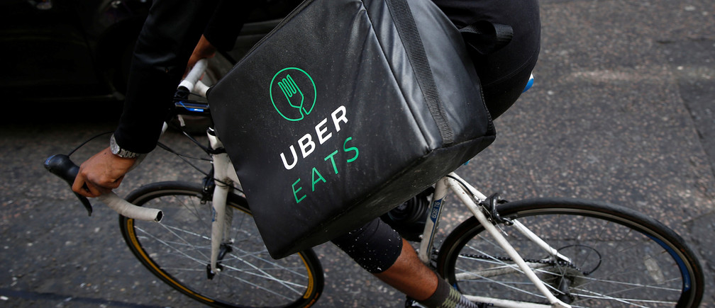 An Uber Eats food delivery courier rides his bike in London.
