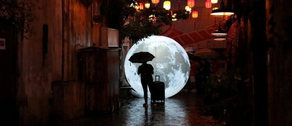 A tourist stands in front of a moon installation ahead of celebrations for the Mid-Autumn Festival at China Town in Kuala Lumpur, Malaysia, August 24, 2019. Picture taken August 24, 2019. REUTERS/Lim Huey Teng     TPX IMAGES OF THE DAY - RC1BA840D500