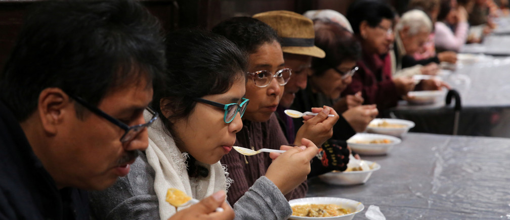 People eat soup called 'porciuncula' during La Porciuncula, a religious activity where Franciscan priests give food to people, at the convent of Los Descalzos, in Lima, Peru, August 2, 2017. REUTERS/Mariana Bazo - RC1D82BDF190