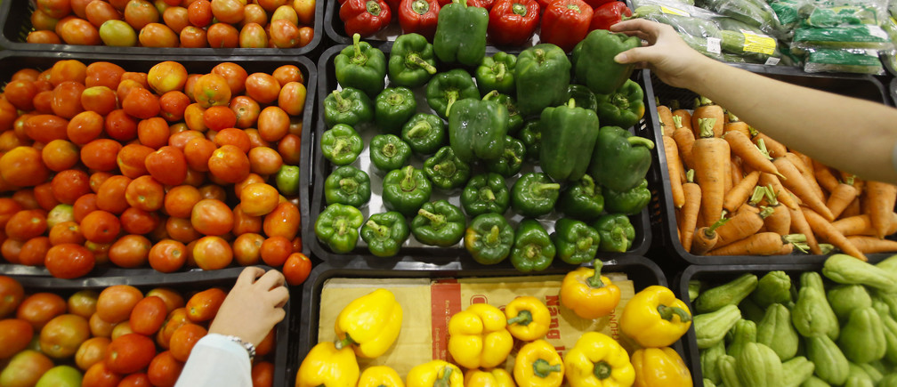 Customers select vegetables at a supermarket in Hanoi September 20, 2014. REUTERS/Kham (VIETNAM - Tags: FOOD BUSINESS) - GM1EA9K1G6V01