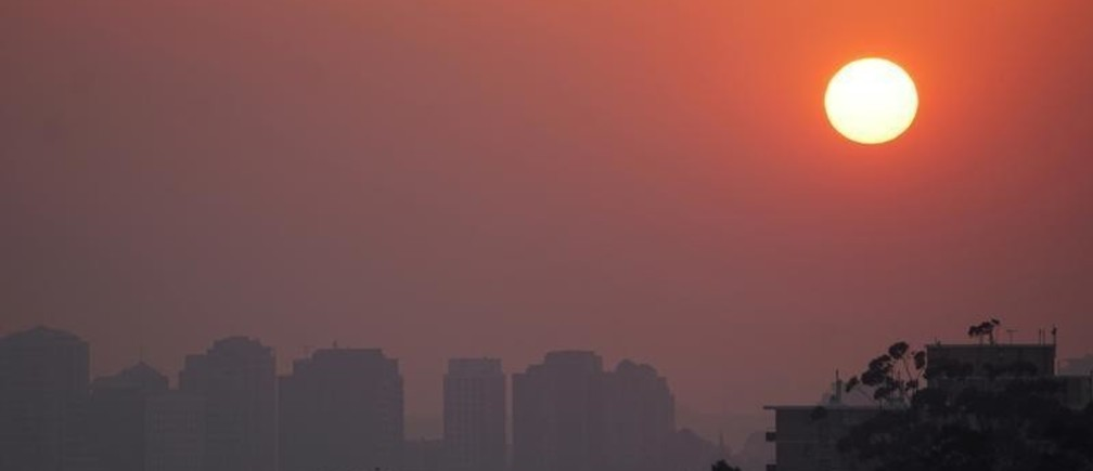 High-rise buildings are seen through smoke from bushfires during sunset in Sydney, Australia, November 11, 2019.   REUTERS/Stephen Coates - RC2X8D9QMWFO