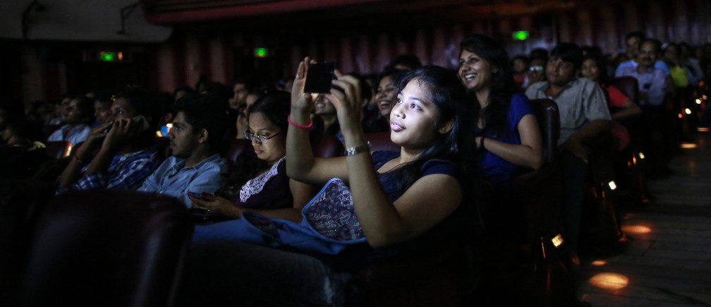"""A cinema goer takes a picture as others watch Bollywood movie """"Dilwale Dulhania Le Jayenge"""" (The Big Hearted Will Take the Bride), starring actor Shah Rukh Khan, inside Maratha Mandir theatre in Mumbai December 12, 2014. T"""