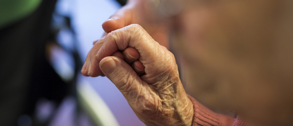 A resident holds the hand of a nurse at the SenVital elderly home in Kleinmachnow outside Berlin May 28, 2013. Facing an acute shortage of skilled applicants among its own workforce, German institutions in the care sector increasingly turn to southern European countries to hire trained nursing staff who are willing to work abroad despite the language barrier in order to escape unemployment at home. The SenVital home for the elderly outside Berlin has accepted five qualified nurses from Spain as their staff, providing eight months of language training and additional care schooling needed to attain the German nursing concession.  Some 100 Spaniards applied for the ten vacancies SenVital had advertised across its various houses.  REUTERS/Thomas Peter (GERMANY  - Tags: HEALTH BUSINESS EMPLOYMENT) - RTX103ZD
