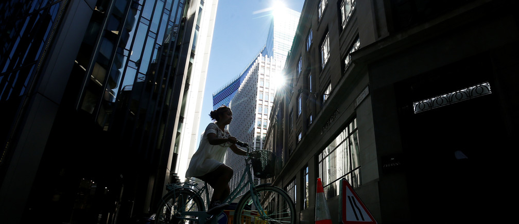 A woman cycles through the financial district in London, following the outbreak of the coronavirus disease (COVID-19), London, Britain, May 6, 2020. REUTERS/Henry Nicholls - RC23JG9J9X4S