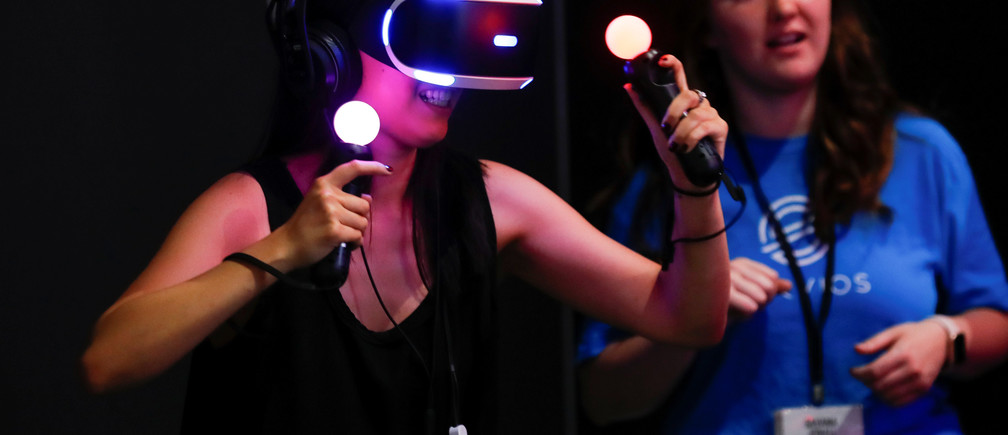 A woman plays a VR game at E3, the world's largest video game industry convention in Los Angeles, California, U.S. June 12, 2018. REUTERS/Mike Blake - RC1CECC10BD0