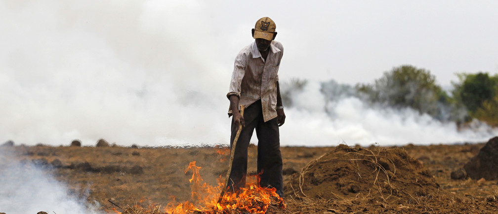 A farmer burns dried grass and twigs on his field near the proposed site of the Jaitapur nuclear plant in Ratnagiri district, about 360 km (224 miles) south of Mumbai, April 13, 2011. Farmers burn dried grass and twigs on the land before the planting season to introduce ash to the soil, a traditional method of increasing soil fertility.  REUTERS/Danish Siddiqui (INDIA - Tags: ENVIRONMENT ENERGY) - GM1E74D1EXK02