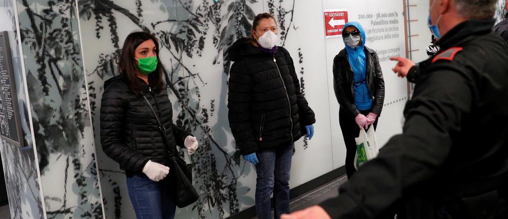 Un guardia de seguridad del metro hace un gesto mientras la gente se para en señales de distanciamiento social mientras esperan un tren en la estación de metro de San Giovanni mientras continúa la propagación de la enfermedad coronavirus (COVID-19), en Roma, Italia, el 28 de abril de 2020.