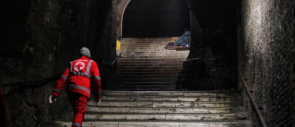 Un trabajador de la Cruz Roja revisa a un indigente acostado en un escalón cerca del Coliseo en Roma, Italia, el 17 de marzo de 2020.