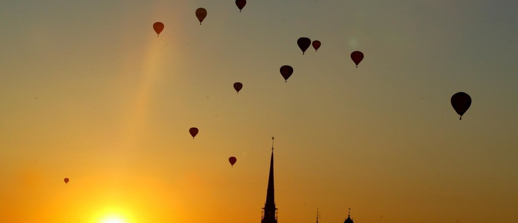 Air balloons sail off into the sunset after participating in a Nordiccompetition over Stockholm, Salt lake, June 5, 2002. The event takes ispart of a week of celebrations for Stockholm's 750th year jubilee. Theballoons dropped markers on targets, floating on the water surface.(SWEDEN, NORWAY, DENMARK OUT) REUTERS/Mark Earthynbw - RP3DRIADVBAA
