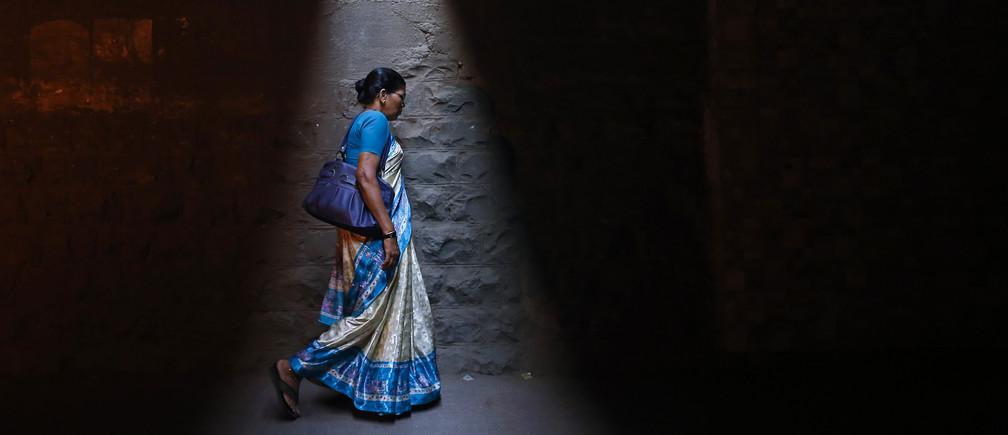 A woman walks through a subway under railway tracks in Mumbai January 7, 2014.