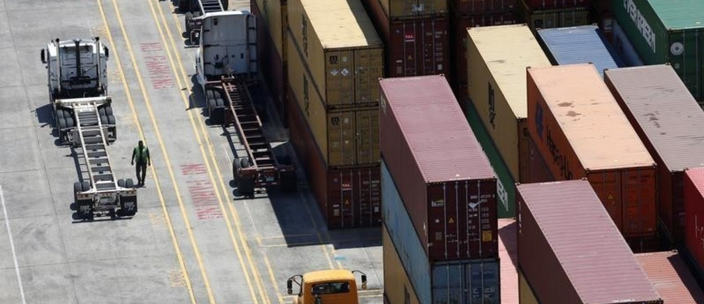 Workers stack empty shipping containers for storage at Wando Welch Terminal operated by the South Carolina Ports Authority in Mount Pleasant, South Carolina, U.S. May 10, 2018. Picture taken May 10, 2018. REUTERS/Randall Hill - RC1212BAF590
