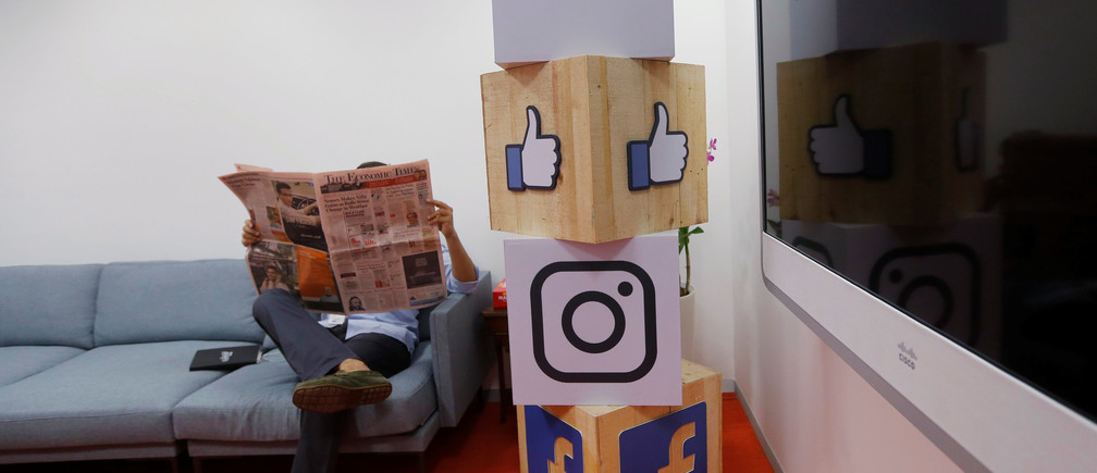 A man reads a newspaper at the reception area of Facebook's new office in Mumbai, India May 27, 2016. REUTERS/Shailesh Andrade - RTX2EGEK