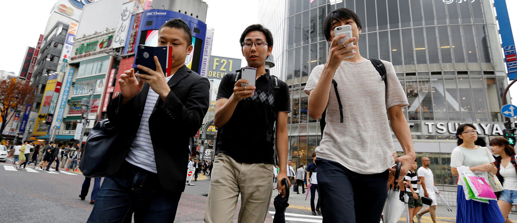 "Men play the augmented reality mobile game ""Pokemon Go"" by Nintendo on their mobile phone as they walk at a busy crossing in Shibuya district in Tokyo, Japan, July 22, 2016."
