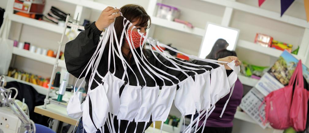 Una mujer sostiene máscaras de tela preventivas en un taller de máquinas de coser, tras el brote de la enfermedad coronavirus (COVID-19) en Concepción, Chile, el 30 de marzo de 2020.