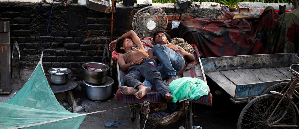 People sleep on a hand cart at a roadside on a hot day in New Delhi, India, June 1, 2018. REUTERS/Amit Dave - RC1BADEA75D0