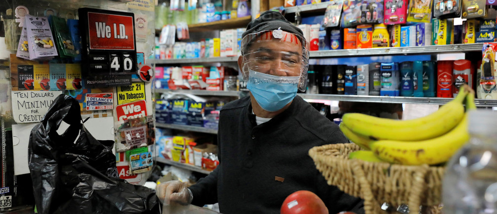Bodega manager Rafael Perez wears a homemade face protector, fashioned from a water bottle, as he works in the Chinese Hispanic Grocery during the coronavirus disease (COVID-19) outbreak in the Lower East Side neighborhood of Manhattan, New York City, New York, U.S., April 2, 2020. REUTERS/Andrew Kelly - RC2FWF9X7P2I