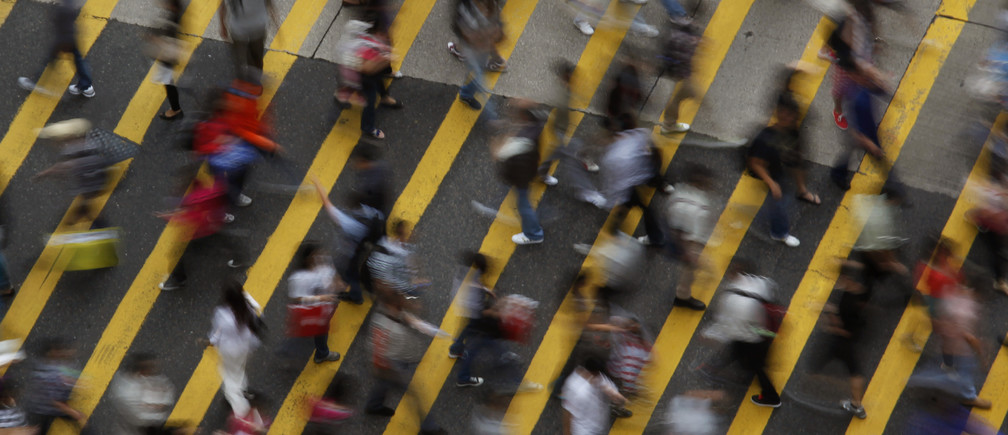 People cross a street in Mong Kok district in Hong Kong, October 4, 2011. Mong Kok has the highest population density in the world, with 130,000 in one square kilometre. The world's population will reach seven billion on 31 October 2011, according to projections by the United Nations, which says this global milestone presents both an opportunity and a challenge for the planet. While more people are living longer and healthier lives, says the U.N., gaps between rich and poor are widening and more people than ever are vulnerable to food insecurity and water shortages.   Picture taken October 4, 2011.   REUTERS/Bobby Yip   (CHINA - Tags: SOCIETY) - LM2E7AE147B01