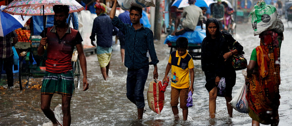 People walk on the water as roads are flooded due to heavy rain in Dhaka, Bangladesh July 26, 2017.