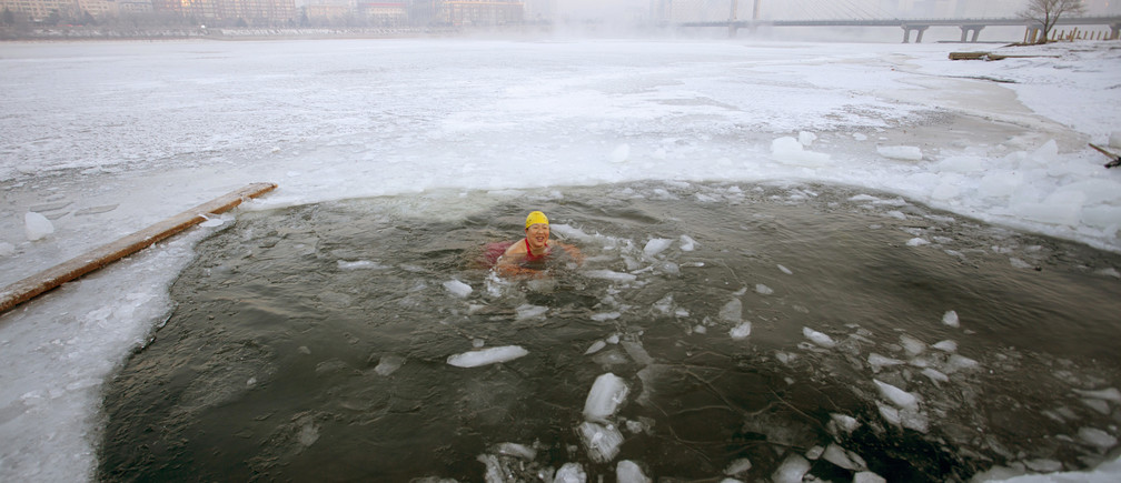 A winter swimmer swims in icy waters after breaking the ice of the frozen Songhua River, in Jilin, Jilin province February 11, 2015. REUTERS/Stringer (CHINA - Tags: ENVIRONMENT SPORT SWIMMING TPX IMAGES OF THE DAY) CHINA OUT. NO COMMERCIAL OR EDITORIAL SALES IN CHINA - GM1EB2B130K01