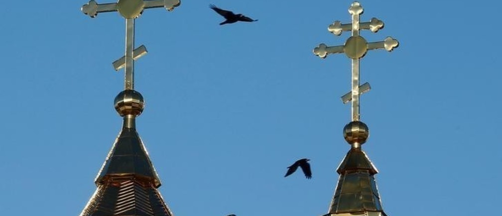 Ravens fly past the crosses of an Orthodox church in the town of Mstislavl, Belarus March 16, 2018. REUTERS/Vasily Fedosenko