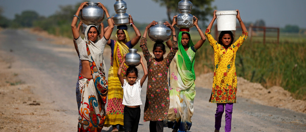 Village women and girls carry water at Fangadi Village on the outskirts of Ahmedabad, India January 27, 2018. Picture taken January 27, 2018. REUTERS/Amit Dave - RC1BD1AA0E40