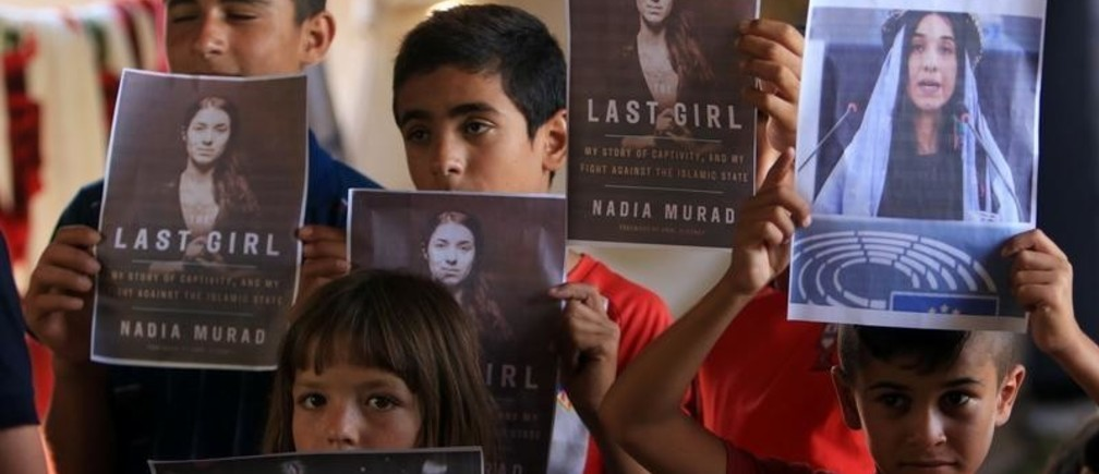 Yazidi children hold pictures of Nadia Murad, who won the Nobel Peace prize, in Duhok, Iraq October 5, 2018.