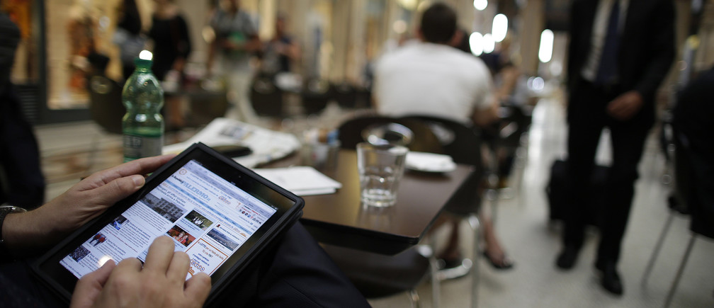 A man poses with his iPad tablet as he sits in a bar, in this photo illustration taken in Rome September 20, 2012.